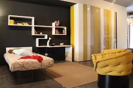 bedroom futuristic bedroom design with simple bed on the metal base and brown rug complete with yellow chair and modern white wall shelf on the black wall