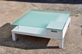 square white lacquer wooden coffee table with glass top and white
