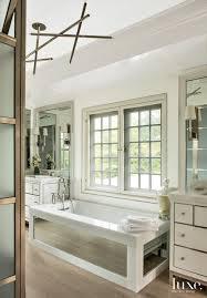 modern white master bathroom with mirror paneled tub luxe