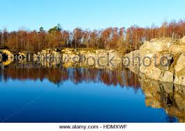 water filled granite quarry in leafless forest in winter