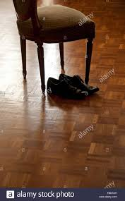 Next Laminate Flooring Men S Black Shoes Next To Old Fashioned Chair On The Wooden Floor