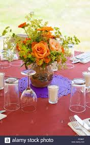 casual table setting with glassware and bouquet of flowers at