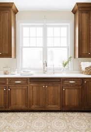 what color countertops go with brown cabinets brown wood laundry cabinets with mosaic floor tiles