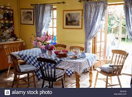 blue checked cloth on table with stick back chairs in yellow