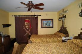 picture of awesome disney pirate ship bed with striped curtain and wooden barrel for nightstand in combination with wooden ceiling fan also pirates logo print on curtains kid room