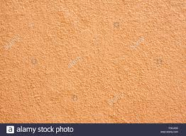 orange stucco textured wall background with natural light stock