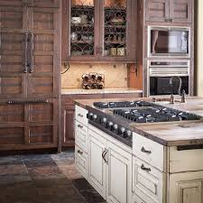 appliances stone tile flooring with kitchen island with stove
