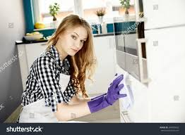 young woman cleaning kitchen cabinets on stock photo 264687632