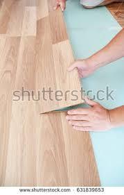 contractor installing wooden laminate flooring insulation stock