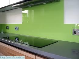 lime green coloured glass splashback in a white kitchen with dark