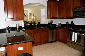 cherry wood kitchen cabinets with black granite cherry wood