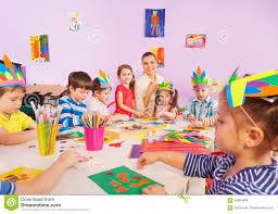children glue paper crafts together with teacher stock photo