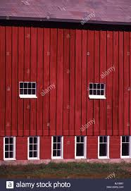 side view of red barn wall with slate roof and eight white framed
