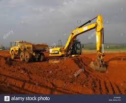 tracked jcb backhoe excavator loading truck on highway