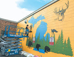 mural signals coming of new hunting store in downtown oxford lake orion artist kristi blattel paints a mural on the front of 40 n washington