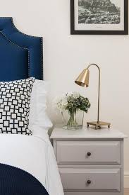 sophisticated bedroom features a blue velvet headboard with silver
