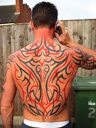 black and red tribal design tattoo on man full back