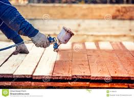 worker painting brown timber renovating exterior wooden fence