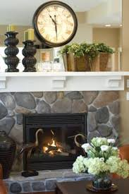 decorate over fireplace with clock and candle holder and plant