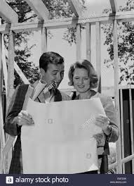 1960s couple looking at house plans blueprints man smoking pipe