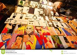 art trader of night market sell many colorful pop art pictures