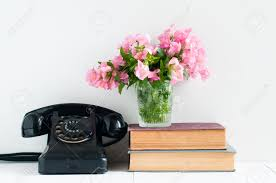 retro home decor a stack of books rotary phone flowers and