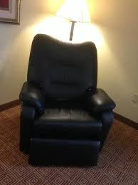 recliner in one corner of room with floor lamp behind picture of