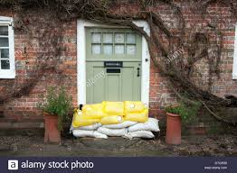 a sage green front door with sand bags flood protection stock