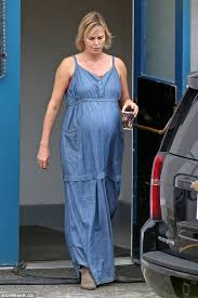 charlize theron dons faux baby bump beneath denim dress while