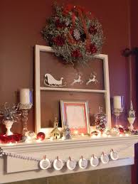 white candles on the glass stand with small houses ornament and