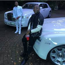 roll royce nigeria photo olamide and davido poses in front of white luxurious rolls