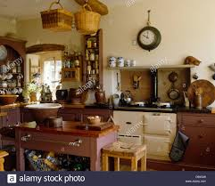 baskets on beam above butchers block and wooden stool in cottage baskets on beam above butchers block and wooden stool in cottage kitchen with clock on wall above cream aga oven