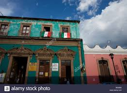 mexican flags hang from the balconies of colonial homes in oaxaca