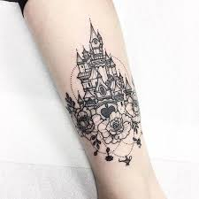 picture of a black ink wrist tattoo with a princess castle and flowers