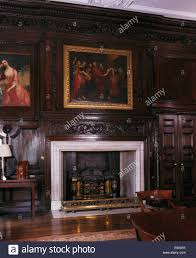 large painting above fireplace in paneled period dining room stock