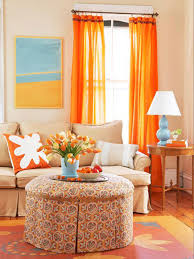 cozy living room with ottoman as coffee table and orange curtains