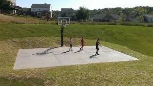 there are three kids playing basketball on their backyard court