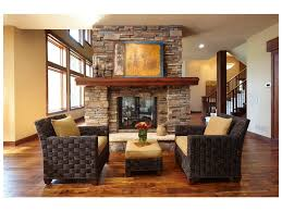 yellow walls wood flooring woven armchairs stacked stone fireplace