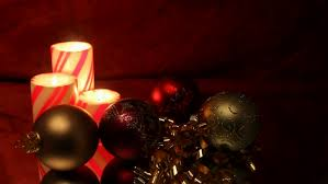 three christmas pillar candles with ornaments and background of