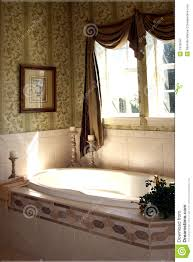 upscale restroom with garden tub and sunlight in new home stock