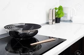 modern kitchen stove frying pan and sticks in modern kitchen with induction stove stock