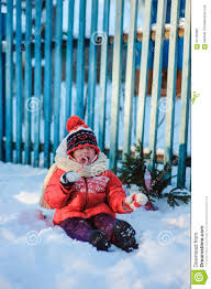 happy child with christmas decorations at wooden fence in