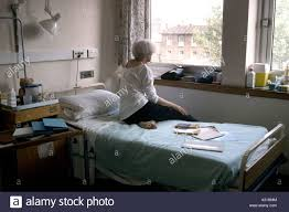 woman seated on her hospital bed in the cancer ward stock photo