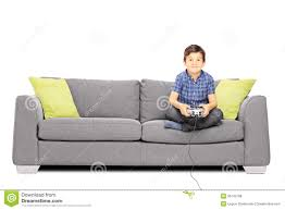 young smiling kid seated on a sofa playing video games stock photo
