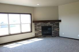 admirable corner fireplace design ideas with stacked stone and dark brown wooden fireplace mantel also grey