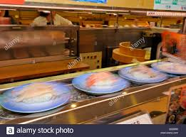 japanese cuisine bar plates with sushi running around on conveyor belt in japanese