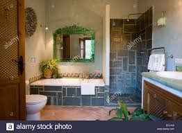 green framed mirror above bath with slate tiled surround in modern