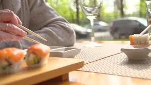 happy couple eating sushi rolls in japan restaurant sushi bar