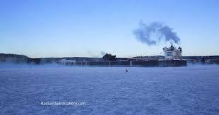 lake superior sea smoke huge ore boat makes its way through frozen lake superior