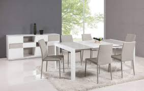 sleek white table with ivorybeige dining chairs top off the